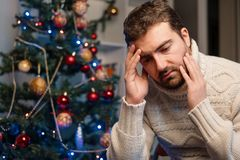 Man felling toothache during the christmas time after eating to Royalty Free Stock Photos