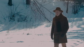 A man in a felt hat and coat comes in the winter woods. brown hat made of felt and a brown coat stock footage