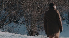 A man in a felt hat and coat comes in the winter woods. brown hat made of felt and a brown coat stock video footage