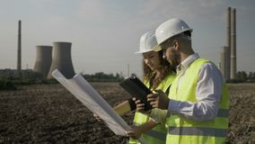 Man and female engineers coworkers analyzing and checking scheme project plans near gas energy factory -. Man and female engineers coworkers analyzing and stock video