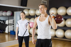 Man With Female Friend Lifting Kettlebell In Gym Stock Photo