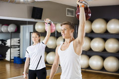 Man With Female Friend Lifting Kettlebell In Gymnasium Royalty Free Stock Image