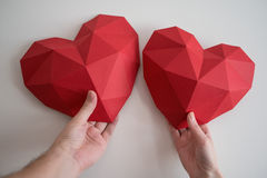 Man and female hands holding red polygonal heart shapes Royalty Free Stock Image