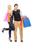 Man and female standing close together and holding shopping bags Stockbild