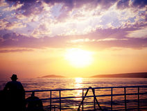 Man on a ferry looking at sunset Stock Photography