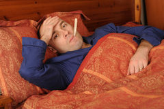 Man with Fever. A sick man having fever with a thermometer in his mouth, lying on the bed Stock Image