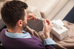 Man with fever checking temperature. Point of view of a young man sick with fever checking his temperature on a thermometer Stock Image