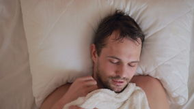 A man with a fever is lying in bed at home stock video footage