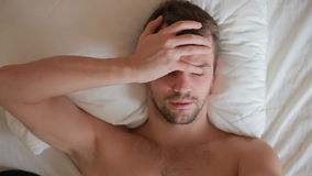 A man with a fever is lying in bed at home stock footage