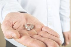 Engagement / marriage / wedding proposal scene. Close up of man handing the expensive gold platinum diamond ring to his bride. Man, fiance, groom to be holds Stock Image