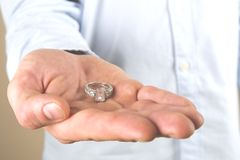 Engagement / marriage / wedding proposal scene. Close up of man handing the expensive gold platinum diamond ring to his bride. Man, fiance, groom to be holds Royalty Free Stock Photography