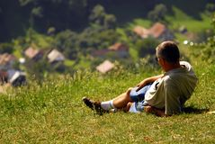 Man on a field. Man admiring a village from the top of a hill Stock Photography