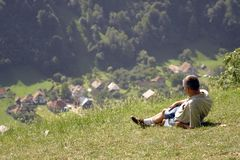 Man on a field. Man admiring a village from the top of a hill Royalty Free Stock Photography