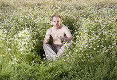 Man  in the field of camomiles guesses on a camomile Stock Photography