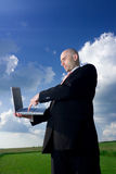 Man in field with laptop. A view of a businessman in a business suit and standing in a large open field, pushing a key on the keyboard of a laptop computer royalty free stock photography