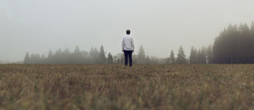 Man in a field looking in direction of a forest  Royalty Free Stock Photography