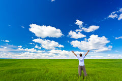 Man on field rising up hands Royalty Free Stock Image