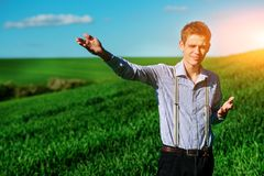 Man on the field shows on elongated hand somewhere far into something.  royalty free stock images