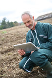 Man in field using tablet for work Stock Photos