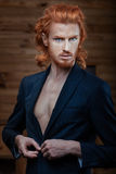 Man with the fiery hair. The man wears a jacket over his naked body, his fiery red hair Stock Photography