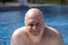 Bald Man in the fifties smiling in the pool-Stock photos. Bald man in the fifties, by the pool, smiling stock images