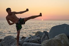 Man in fighting pose and sunset over the ocean. Sochi, Russia stock images