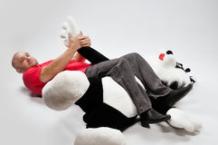Man fights with a toy animal Stock Images