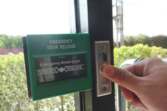 Man figure press the bottom the emergency door release. Man fingure is pressing /opening the emergency fire exit door royalty free stock photography