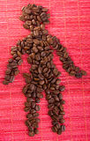 Man figure shape by coffee beans on a mat. Heap of roasted coffee beans placed on bamboo man in shape of man figure Stock Photography