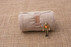 Man figurine in hand on linen canvas background Royalty Free Stock Photo
