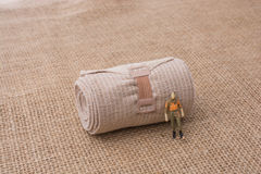 Man figurine in hand on linen canvas background Stock Photo