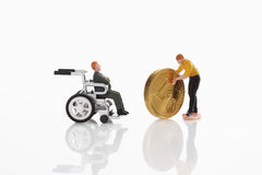 Man figurine moving euro coin towards man figurine in wheel chair Royalty Free Stock Photo