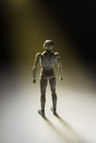 Man figurine standing in powerful pose looking up with beam of l Royalty Free Stock Photo