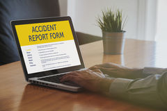 Man fill in an accident report form with a laptop by internet. Royalty Free Stock Photography