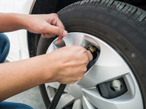 Man filling air pressure in the car tyre Royalty Free Stock Images