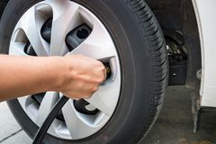 Man filling air pressure in the car tyre Royalty Free Stock Photo