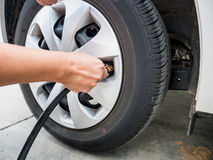Man filling air pressure in the car tyre Royalty Free Stock Image