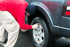 Man filling air to tire on a rainy day stock image