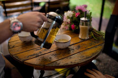 Man filling a cup with tea in summer cafe Royalty Free Stock Photos