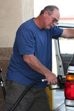 Man filling expensive gas tank. A man fills his gas tank of his SUV with expensive fuel in the united states Stock Photos
