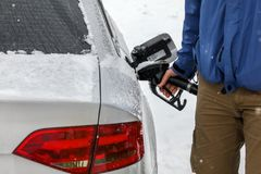 Man filling fuel to his diesel car at gas station in winter. Detail on snow covered tank cover and pump nozzle.  royalty free stock image