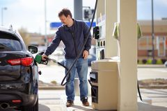 Man filling gasoline fuel in car. Holding nozzle Royalty Free Stock Photos