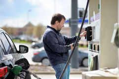 Man filling gasoline fuel. In car holding nozzle Stock Images