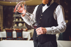 Man filling glass with red wine. Bearded waiter is pouring ruby beverage from carafe into fragile goblet royalty free stock photo