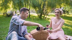 Man filling glasses with ruby wine and saying toast to beloved, anniversary. Stock footage stock footage