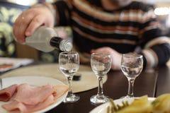 Man filling glasses of vodka Stock Photography