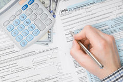 Man filling out 1040 US Tax Form - view from top - studio shot Royalty Free Stock Image