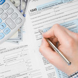 Man filling out 1040 US Tax Form - view from top - 1 to 1 ratio Royalty Free Stock Photo