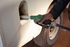 Man filling petrol in car at petrol pump. Close-up of man filling petrol in car at petrol pump stock images