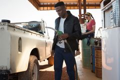 Man filling petrol in car while woman sitting at petrol pump station. On a sunny day Stock Photo